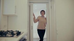 De aantrekkelijke jonge vrouw treft voor het reizen voorbereidingen thuis terwijl inpakkende koffer stock videobeelden
