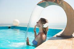 De aantrekkelijke jonge vrouw verfrist zich in pool Stock Afbeelding