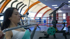 De aantrekkelijke jonge vrouw werkt op een geschiktheidspost die uit in gymnastiek, ijzer pompen Uitgaande vrouw opleiding met pu stock afbeelding