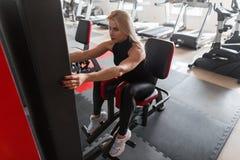 De aantrekkelijke jonge vrouw in zwarte sportkleding in witte tennisschoenen werkt zitting op een moderne simulator in de gymnast royalty-vrije stock foto's