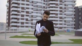 De aantrekkelijke jonge zakenman in zwart kostuum gooit documenten weg openlucht stock videobeelden