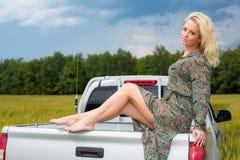 De aantrekkelijke jonge zitting van de blondevrouw op auto Royalty-vrije Stock Foto's