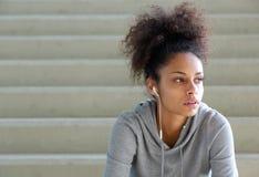 De aantrekkelijke jonge zitting van de sportenvrouw op stappen met oortelefoons stock afbeelding