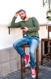 De aantrekkelijke jonge zitting van de hipsterkerel in koffie stock fotografie
