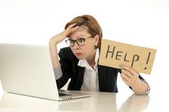 De aantrekkelijke jongelui overweldigde en frustreerde bedrijfsvrouw die aan haar computer werken om hulp vragen stock afbeeldingen
