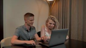 De aantrekkelijke Kerel en het meisje zitten online op de coucandwinkel met creditcard op het laptop notitieboekje stock videobeelden