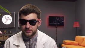 De aantrekkelijke kerel met baard die zonnebril en witte laboratoriumlaag dragen spreekt vreugdevol stock video