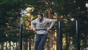 De aantrekkelijke kerel oefent in openlucht het gebruiken van rekstok uit leverend inspanning om spieren te verbeteren en macht t stock video
