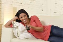 De aantrekkelijke Latijnse laag die van de vrouwen thuis bank en gelukkige het letten op televisie glimlachen lachen Stock Foto