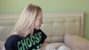 De aantrekkelijke luie blondevrouw gaat bed in vroege ochtend weg stock videobeelden