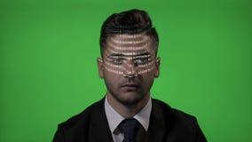 De aantrekkelijke mannelijke hakker kleedde zich als zakenman die blockchain code hebben die zijn gezicht op een groene het scher stock video