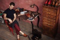 De aantrekkelijke meester past schoenpoetsmiddel met een borstel toe royalty-vrije stock afbeelding
