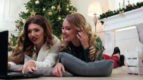 De aantrekkelijke Meisjes, gebruikend laptop en glimlachend bij camera, de Winterweekend verfraaiden dichtbij open haard tijdens  stock video