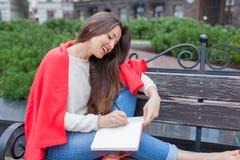 De aantrekkelijke meisjeszitting op een bank met naakte die voeten, met een rode deken, in de nieuwe woonwijk worden behandeld en stock foto