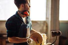 De aantrekkelijke mens begint doend houtbewerking in timmerwerk stock foto's