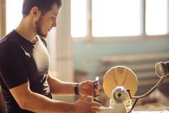 De aantrekkelijke mens begint doend houtbewerking in timmerwerk stock foto