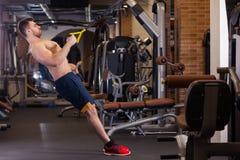 De aantrekkelijke Mens doet Crossfit-Duw UPS met Trx-Geschiktheidsriemen in de Gymnastiek` s Studio stock afbeeldingen