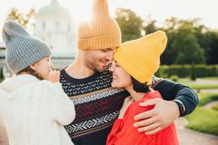 De aantrekkelijke mens draagt gele warme hoed, omhelst zijn vrouw en de dochter, bekijkt hen met grote liefde Het aanbiddelijke m royalty-vrije stock afbeelding
