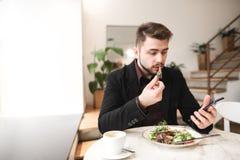 De aantrekkelijke mens in een kostuum zit in een comfortabel restaurant die, die salade met een plaat eten en een smartphone gebr stock foto's