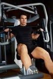 De aantrekkelijke mens in een zwarte T-shirt en een sportkleding is bezig geweest met de gymnastiek stock foto's
