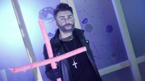 De aantrekkelijke mens met leuk kapsel in leer danst en zingt met roze kruis stock videobeelden