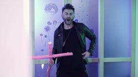 De aantrekkelijke mens met modieuze haarbesnoeiing in leerjasje danst holdings roze kruis stock footage