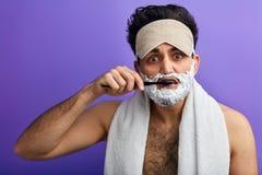 De aantrekkelijke mens met scheercrème op zijn gezicht behandelt zijn tanden stock afbeeldingen