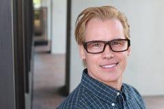De aantrekkelijke mens met zijn haar kleurde blond en een perfecte glimlach dragend glazen Royalty-vrije Stock Foto's