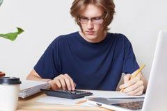 De aantrekkelijke mens ziet financiële crisis onder ogen, bestudeert bericht van bank, berekent cijfers De mannelijke student bes Stock Foto's