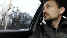 De aantrekkelijke mens zit in een auto en kijkt uit het venster stock video