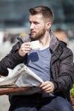 De aantrekkelijke mens zit in een koffiewinkel lezend het nieuwsdocument Royalty-vrije Stock Foto