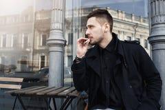 De aantrekkelijke mens in zwarte kleren nam zit om te hebben cigarete royalty-vrije stock afbeelding