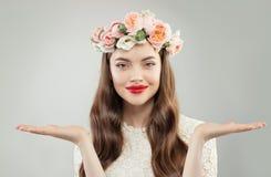 De aantrekkelijke Model Lege Open Handen van Woman Showing Two op Witte Achtergrond Duidelijke Huid, Krullend Haar, Make-up en Bl stock foto