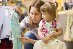 De aantrekkelijke moeder toont haar dochter een mooie kleding Royalty-vrije Stock Foto