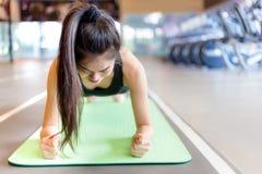De aantrekkelijke mooie vrouw doet dat oefening op een yogamat bij royalty-vrije stock foto's