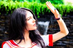 De aantrekkelijke mooie vrouw heft hand voor het beschermen van sterke sunl op stock foto's