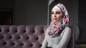 De aantrekkelijke moslimvrouw in heldere mooie hijab zit op bank stock video