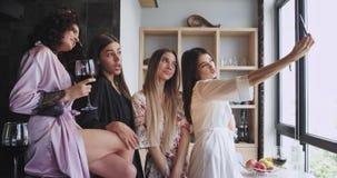 De aantrekkelijke multi etnische dames in pyjama's in stedelijke ontwerpstudio nemen de selfievideo gebruikend een smartphone ter stock video