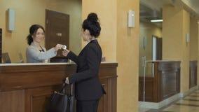De aantrekkelijke onderneemster krijgt een sleutel van een ruimte in een hotel stock video