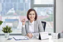 De aantrekkelijke onderneemster zit bij bureau met computer en kalender in het bureau stock afbeelding
