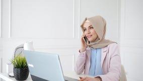 De aantrekkelijke ontspannen moslimvrouw spreekt mobiele telefoonzitting op haar werkplaats stock videobeelden