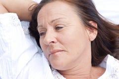 Droevige overwegende rijpe vrouw die in bed rusten Royalty-vrije Stock Afbeelding