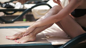 De aantrekkelijke sexy vrouw sunbed dichtbij de pool die de lotion van het zonblok op haar lichaam toepassen stock footage