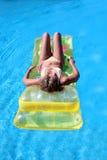 De aantrekkelijke, slanke jonge dame die op opblaasbaar liggen sunbed op swimmi stock fotografie