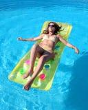 De aantrekkelijke, slanke jonge dame die op opblaasbaar liggen sunbed op swimmi stock afbeeldingen