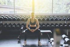 De aantrekkelijke slanke vrouwenzitting bij gymnastiek in de ochtend, Aziatische vrouwelijke onderbreking en ontspant na training stock foto's