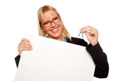 De aantrekkelijke Sleutels van de Holding van de Blonde & Leeg Wit Teken Stock Foto's
