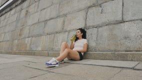 De aantrekkelijke sportieve dame drinkt water stock footage