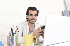 De aantrekkelijke student of hipster stileert freelancer zakenman het werken met laptop computer en mobiele telefoon royalty-vrije stock afbeelding