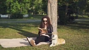 De aantrekkelijke studente leest boekzitting op plaid onder boom in stadspark met haar dichtbij en puppy die liggen genieten van stock footage